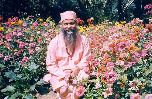 Swami Brahmananda Giri assis parmi des fleurs roses