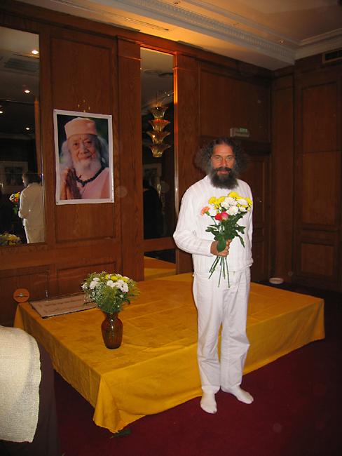 Peter Baba tenant des fleurs lors du Centenaire de Paramahamsa Hariharananda au programme de Kriya Yoga de Paris en novembre 2006