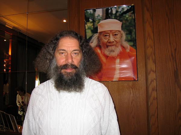 Rajarshi Peter Baba debout devan la photo de Hariharananda au programme de Kriya Yoga de Paris en mars 2006