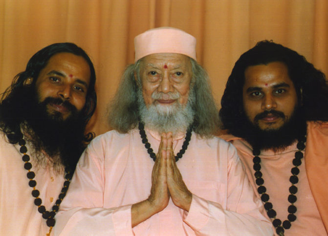 Paramahamsa Hariharananda assis les mains jointes entouré de Prajnanananda et Suddhananda