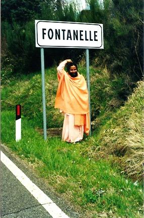 Paramahamsa Prajnanananda amusé montre du doigt sa fontanelle sous le panneau de signalisation routière de la ville Fontanelle